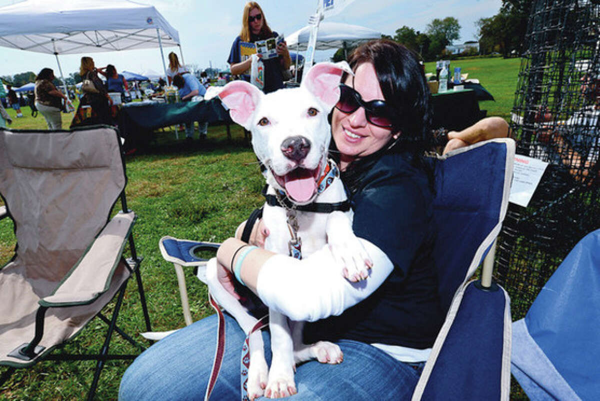 Hour photo / Erik Trautmann Rachel Pagliarulo and Thor of Bully Breed Rescue greet people and their pets as they enjoy the PAWS 50th Anniversary Festival at Taylor Farm Park in Norwalk Saturday.
