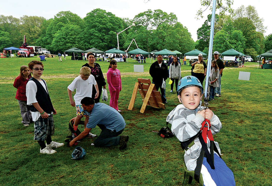 Alejandro Cardenas climbs a tree at The 7th annual Norwalk Wilton Tree Festival at Cranbury Park Saturday. Hour photo / Erik Trautmann / (C)2013, The Hour Newspapers, all rights reserved