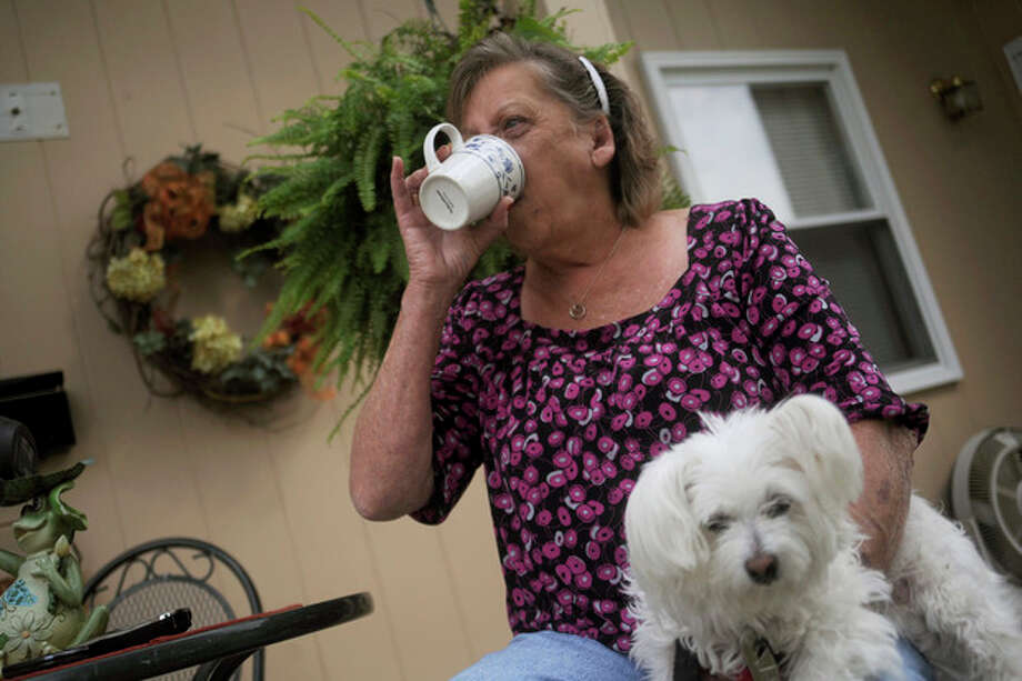 CORRECTS TYPE OF MENINGITIS TO FUNGAL INSTEAD OF BACTERIAL - Patsy Bivins, 68 of Sturgis, Ky., drinks coffee while sitting on her porch with her dog Little Britches at her apartment in Sturgis, Ky., Friday, October 5, 2012. Bivins was injected with steroids at St. Mary Sugricare in Evansville, Ind., who notified her of possibly being infected with fungal Meningitis. (AP Photo/Stephen Lance Dennee) / FR170568 AP