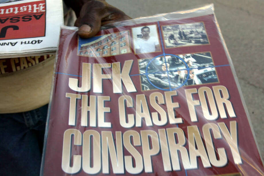 """FILE - In this Saturday, Nov. 8, 2003 file photo, a vendor holds up a magazine-style publication titled """"JFK The Case For Conspiracy"""" in downtown Dallas. (AP Photo/Donna McWilliam)"""