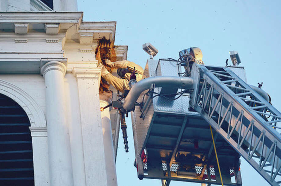 Hour photo / Erik TrautmannBeekeepers Andrew and Norm Cote rescue a hive of honey bees that had nested in the eaves of the steeple of the First Congregational Church on the Green in Norwalk. / (C)2012, The Hour Newspapers, all rights reserved