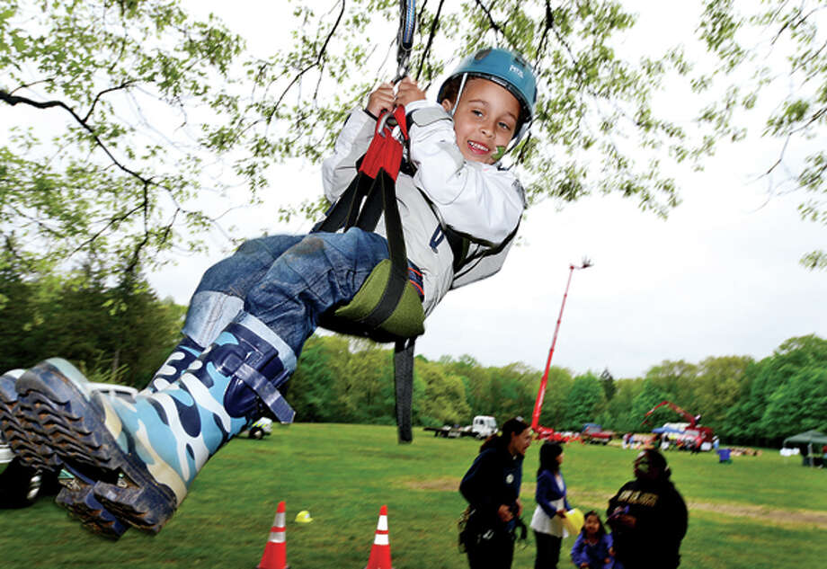 Aadi Neujhar, 4, goes up in a tree at The 7th annual Norwalk Wilton Tree Festival at Cranbury Park Saturday. Hour photo / Erik Trautmann / (C)2013, The Hour Newspapers, all rights reserved