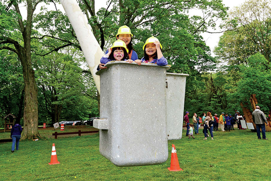 Junhua Zheng and her daughters Sofia, 4, and Alyssa, 5, go up in a Care of Trees maintenance bucket at The 7th annual Norwalk Wilton Tree Festival at Cranbury Park Saturday. Hour photo / Erik Trautmann / (C)2013, The Hour Newspapers, all rights reserved