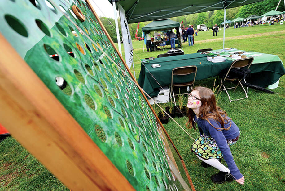 Olivia Landau tries her hand at a maze game, one of the many activities at The 7th annual Norwalk Wilton Tree Festival at Cranbury Park Saturday. Hour photo / Erik Trautmann / (C)2013, The Hour Newspapers, all rights reserved