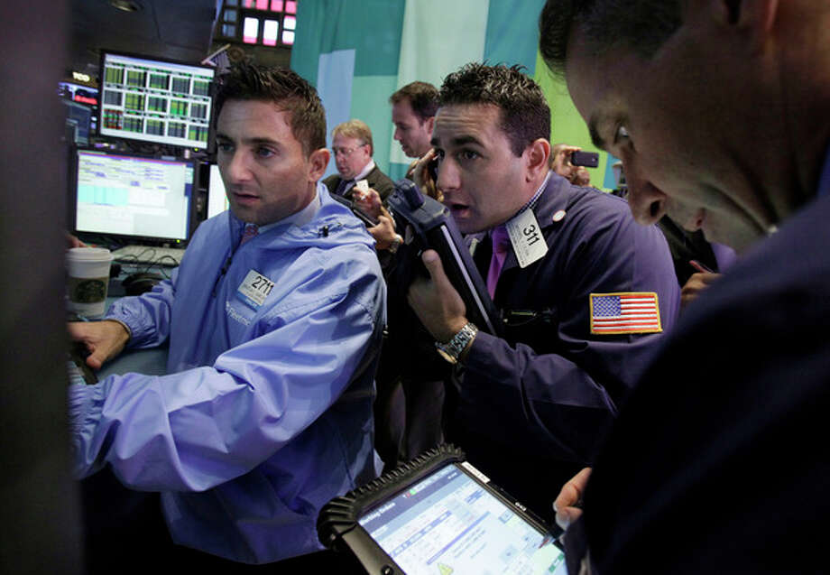 Trader Michael Liloia, center, works on the floor of the New York Stock Exchange Friday, Oct. 5, 2012. Stocks are rising in early trading on Wall Street after the government reported that the U.S. unemployment rate fell below 8 percent for the first time in almost four years. (AP Photo/Richard Drew) / AP