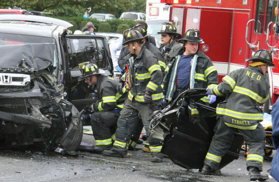 Hour Photo by Chris BosakNorwalk firefighters lift the roof off of a Honda SUV following an accident on North Avenue (US Route 1) in Norwalk on Monday afternoon. Five victims were transported to Norwalk Hospital, but no serious injuries were reported.