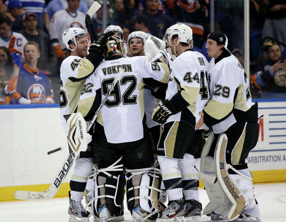 Pittsburgh Penguins, including defenseman Brooks Orpik (44), celebrate with goalie Tomas Vokoun (92), of the Czech Republic, after Orpik scored in overtime of Game 6 of the team's first-round NHL Stanley Cup playoff hockey series against the New York Islanders in Uniondale, N.Y., Saturday, May 11, 2013. The Penguins won 4-3, and advanced to the Eastern Conference semifinals. (AP Photo/Kathy Willens) / AP