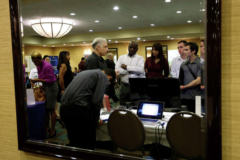 FILE - In this Monday, Sept 17, 2012, file photo, Robert Orkin of the company TxT-Alert, third from left, talks with job seekers during a job fair held by National Career Fairs in Fort Lauderdale, Fla. The U.S. unemployment rate fell to 7.8 percent last month, dropping below 8 percent for the first time in nearly four years. (AP Photo/Lynne Sladky, File) / AP