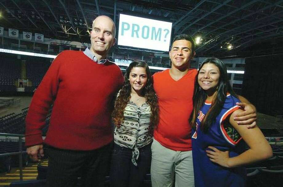 Hour Photo/Alex von Kleydorff. L-R Webster Bank Arena Director of Communications Michael Foley, Vanessa Morales, Kevin Morales and Jessica Jaramillo gather under the jimbo screen with the prom question Jessica proposed to Kevin, it was Vanessa's idea and with help from Michael he said yes. / 2013 The Hour Newspapers