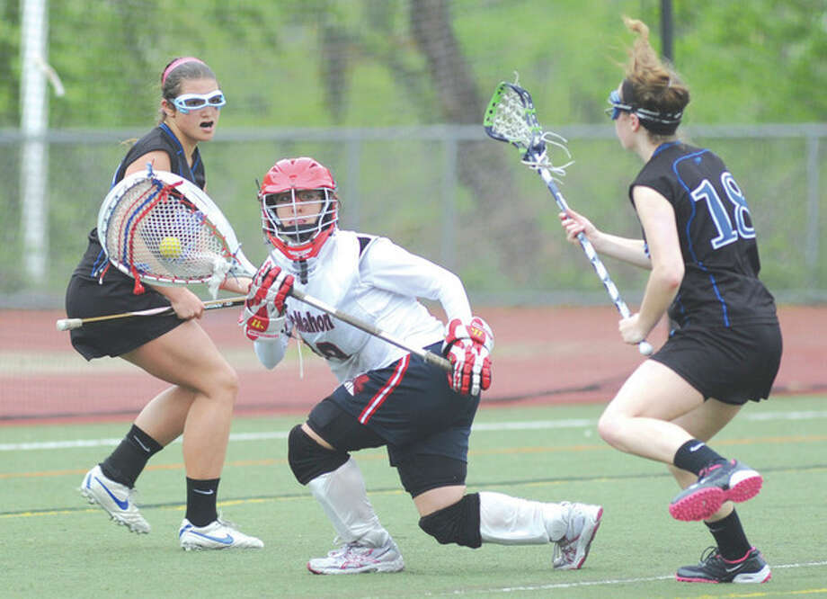 Hour photo/John NashBrien McMahon girls lacrosse goalie Michele Petrucci reverses direction to avoid two Bunnell Bulldog defenders during Saturday's game in Norwalk.