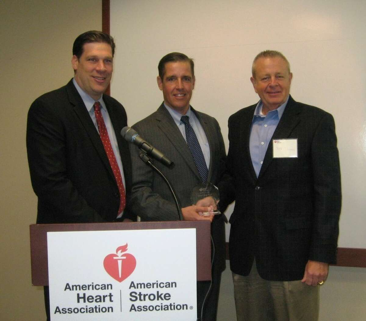 Gregory Plage, American Heart Association executive director, and Matt Fair, regional sales director of First Niagara Risk Management, present the AHA's 2012 Lifestyle Change Award to Jeffrey Thomas, president of corporate operations at Connolly, Inc. in Wilton.