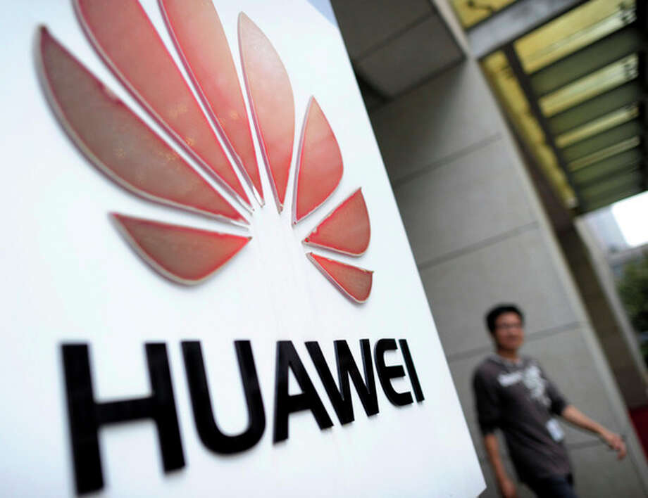 In this Monday, Oct. 8, 2012 photo, a man walks near a logo at a R&D center of Huawei Technologies Inc. in Wuhan, in central China's Hubei province. Eager to expand in the United States, China's biggest technology companies face American anxiety about security and rising Chinese competition. (AP Photo) CHINA OUT / CHINATOPIX