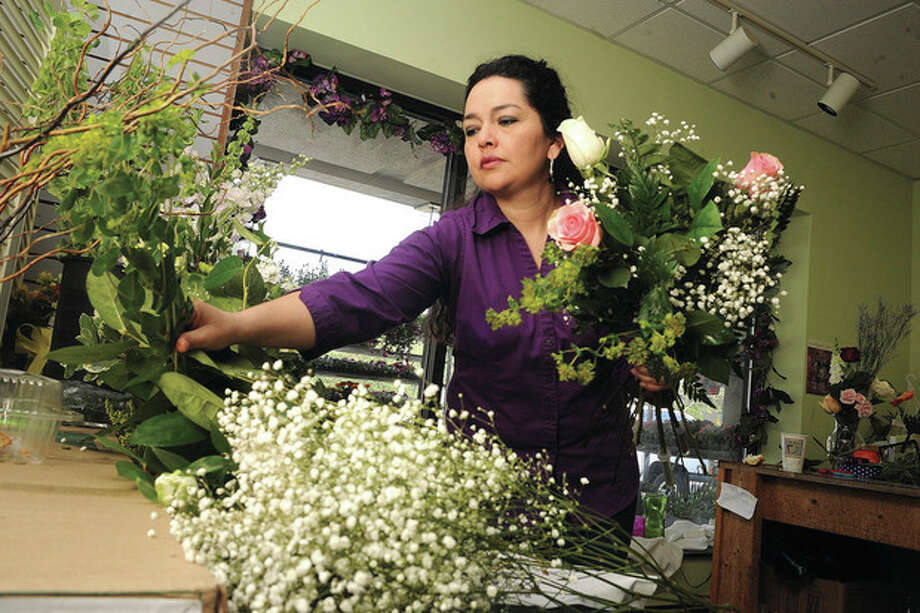 Teresa Brancato arranges a traditional Mother's Daybouquet of of pink and white roses Sunday at Bruce's Flowers in Norwalk for the morning rush of flower orders. hour photo/Matthew Vinci