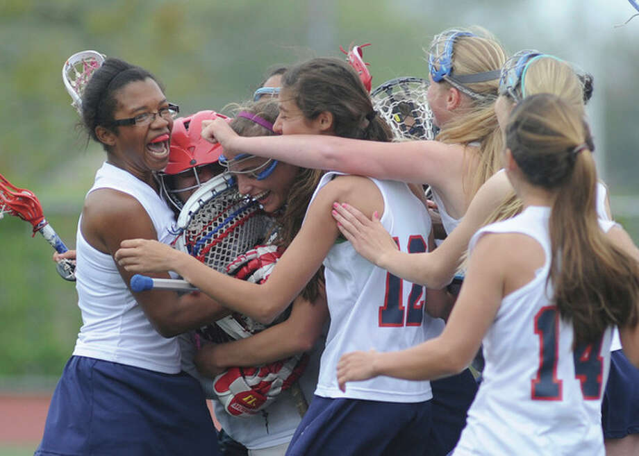 Hour photo/John NashBrien McMahon girls lacrosse goalie Michele Petrucci, second from left in red helmet, is mobbed by teammates, including senior Gabbie Robinson, left, after backstopping McMahon's 12-6 win over Bunnell on Saturday. The win snapped a 29-game losing streak by McMahon.