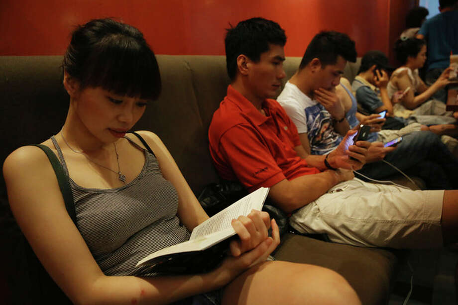 A young Vietnamese girl reads a book while other youngsters use smart phones to go online at a cafe in Ha Noi, Viet Nam Wednesday, May 14, 2013. Close to a third of Vietnam's 90 million people are online and men and women browsing phones and tablets are ubiquitous in the cafes of its towns and cities. The country's potential for growth, young population and good Internet infrastructure have made it an attractive destination for regional and international investors and startups in content provision, e-payment and other services. (AP Photo/Na Son Nguyen). / AP