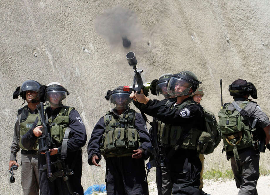 "An Israeli border policeman fires a tear gas grenade during a Palestinian rally to commemorate the 1948 creation of the Israeli state known in Arabic as ""Nakba Day"", or ""Day of the Catastrophe"" outside the West Bank town of Bethlehem, Tuesday, May 14, 2013. (AP Photo/Nasser Shiyoukhi) / AP"