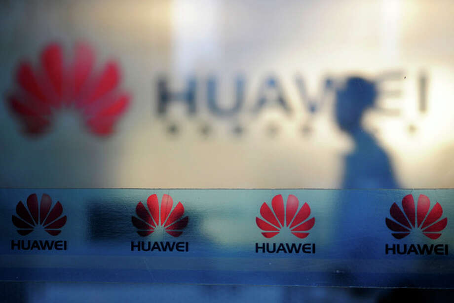 In this Monday, Oct. 8, 2012 photo, a man walks near company logos at a R&D center of Huawei Technologies Inc. in Wuhan, in central China's Hubei province. Eager to expand in the United States, China's biggest technology companies face American anxiety about security and rising Chinese competition. (AP Photo) CHINA OUT / CHINATOPIX