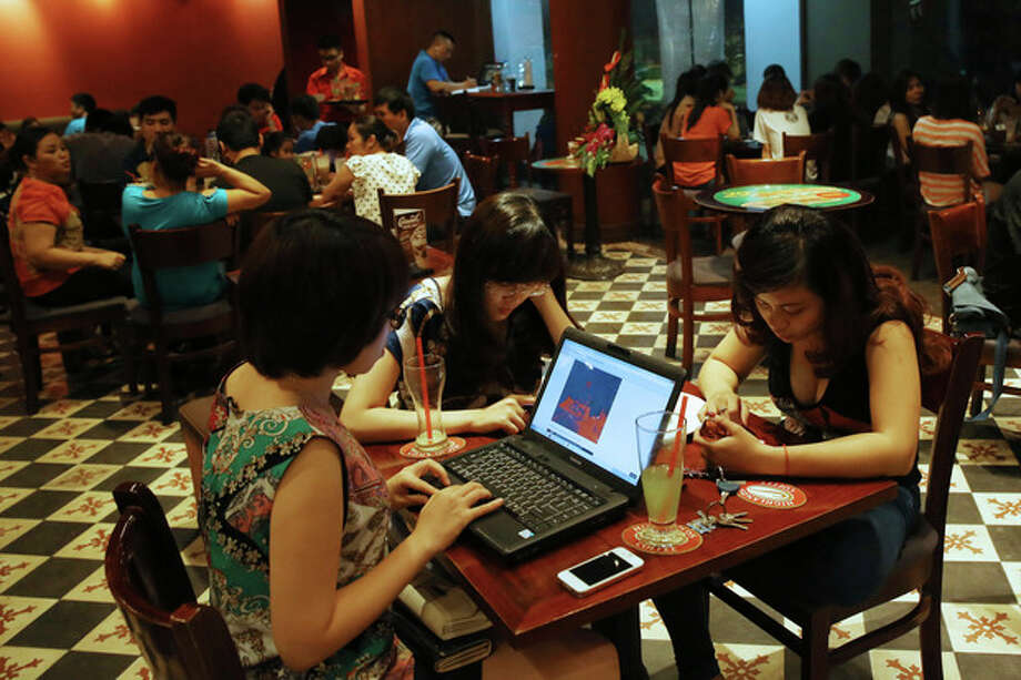 Three young Vietnamese girls use a laptop and smart phones to go online at a cafe in Ha Noi, Viet Nam Wednesday, May 14, 2013. Close to a third of Vietnam's 90 million people are online and men and women browsing phones and tablets are ubiquitous in the cafes of its towns and cities. The country's potential for growth, young population and good Internet infrastructure have made it an attractive destination for regional and international investors and startups in content provision, e-payment and other services. (AP Photo/Na Son Nguyen). / AP
