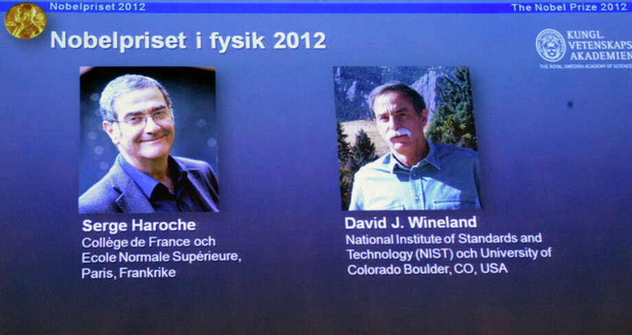 Photographs of the 2012 Nobel Prize laureates in Physics Serge Haroche from France, left, and David Wineland from the US are presented on a screen during a media conference at the Royal Swedish Academy of Science in Stockholm, Sweden, Tuesday Oct. 9, 2012. Frenchman Serge Haroche and American David Wineland have won the 2012 Nobel Prize in physics for inventing and developing methods for observing tiny quantum particles without destroying them. (AP Photo/Bertil Enevag Ericson/SCANPIX) SWEDEN OUT / SCANPIX SWEDEN