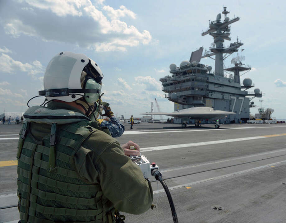In this image provided by the U.S. Navy, Dave Lorenz, a Northrop Grumman deck operator, drives an X-47B Unmanned Combat Air System demonstrator using an arm-mounted controller on the flight deck of the aircraft carrier USS George H.W. Bush Friday May 10, 2013. The George H.W. Bush is scheduled to be the first aircraft carrier to catapult launch an unmanned aircraft from its flight deck Tuesday May 14, 2013. (AP Photo/US Navy, Specialist 2nd Class Timothy Walter) / US Navy