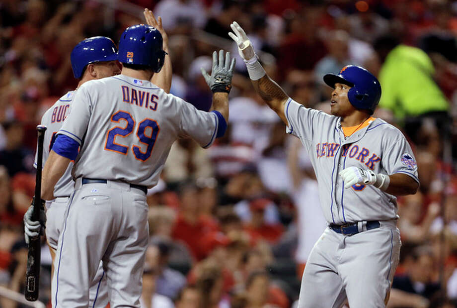New York Mets' Marlon Byrd, right, is congratulated by teammates John Buck, left, and Ike Davis (29) after hitting a two-run home run during the sixth inning of a baseball game against the St. Louis Cardinals on Tuesday, May 14, 2013, in St. Louis. (AP Photo/Jeff Roberson) / AP