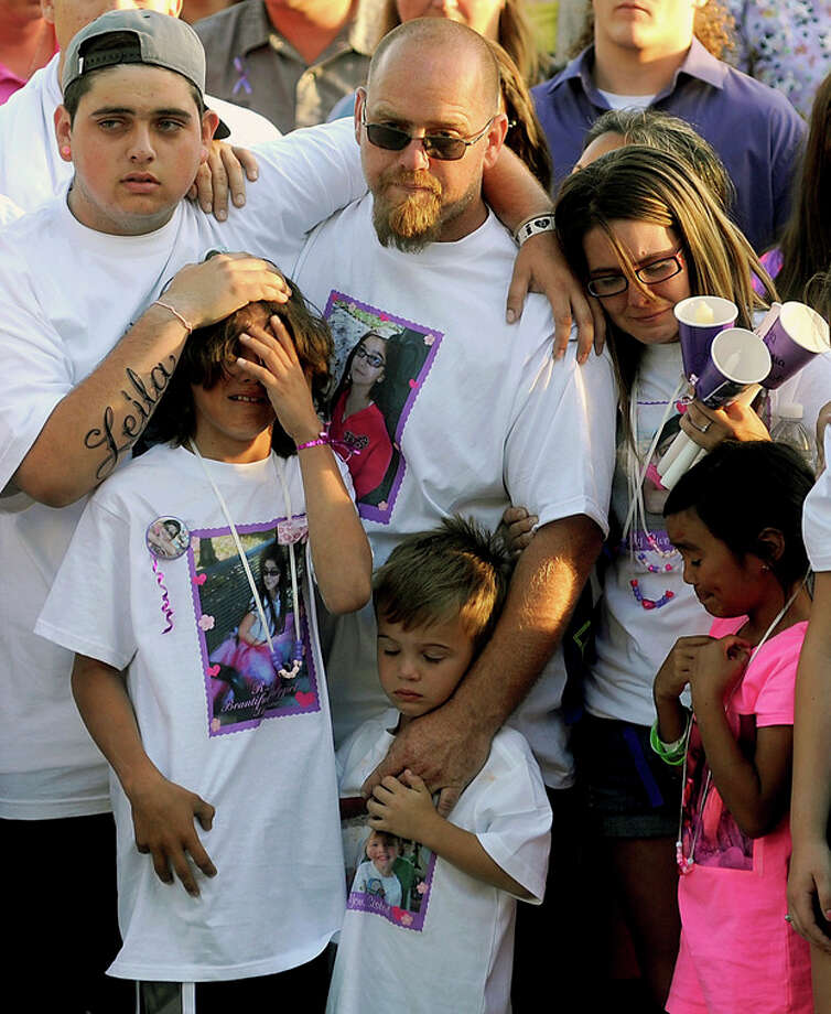"File - In this Tuesday, April 30, 2013 file photo, the family of slain 8-year-old girl Leila Fowler attend a vigil held for her at Jenny Lind Elementary School in Valley Springs, Calif. Leila's father, Barney Fowler, center, stands with Leila's mother Crystal Walters, right, at his shoulder. The father of a 12-year-old boy arrested in the stabbing death of his 8-year-old sister says he believes his son is innocent until he is shown evidence that proves otherwise. Barney Fowler said on Monday May 13, 2013 that the family is standing behind the boy ""until they have the proper evidence to show it's my son."" Sheriff's deputies in the Central California foothill community of Valley Springs arrested the 12-year-old on Saturday in the April 27 death of 8-year-old Leila Fowler. (AP Photo/The Modesto Bee, Elias Funez, File) / The Modesto Bee"