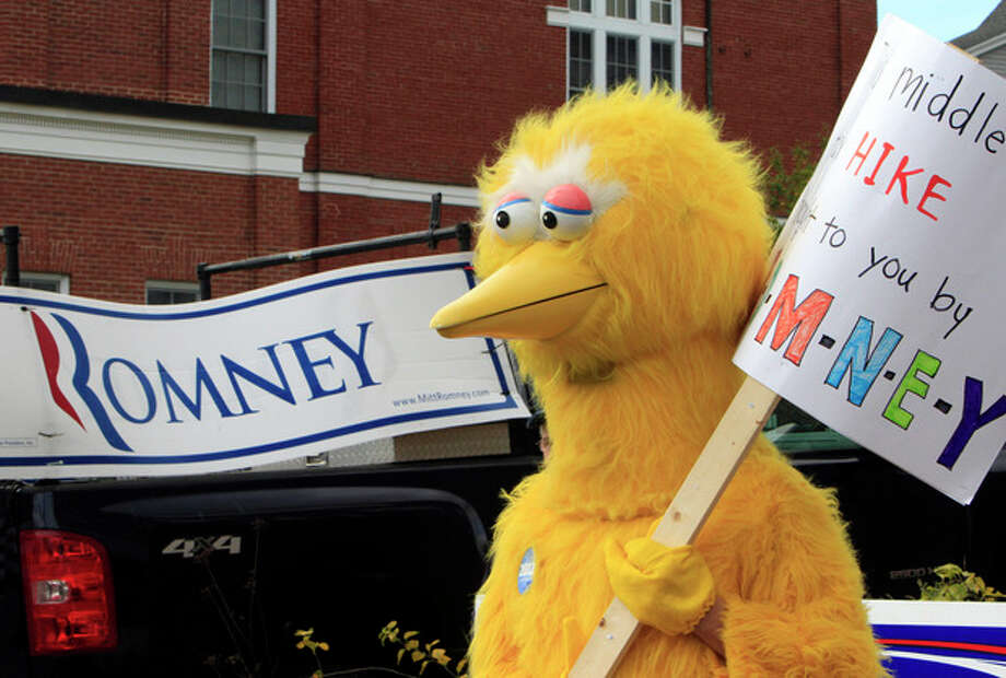 A person dressed as Big Bird holds a sign outside Republican presidential candidate, former Massachusetts Gov. Mitt Romney's headquarters, Monday, Oct. 8, 2012 in Derry, N.H. where House Speaker John Boehner of Ohio was about to speak to supporters. (AP Photo/Jim Cole) / AP