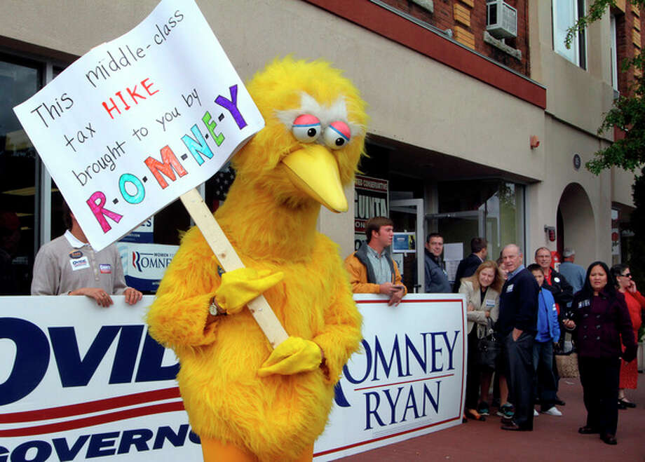 A person dressed up as Big Bird holds a sign against Republican presidential candidate, former Massachusetts Gov. Mitt Romney outside the Romney headquarters, Monday, Oct. 8, 2012 in Derry, N.H. where House Speaker John Boehner of Ohio was about to speak to supporters. (AP Photo/Jim Cole) / AP