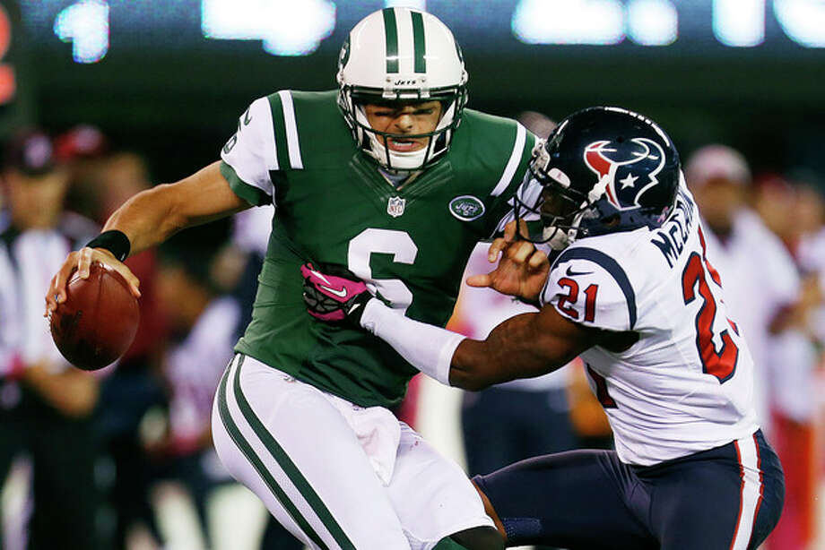 Houston Texans defensive back Brice McCain (21) sacks New York Jets quarterback Mark Sanchez (6) during the second half of an NFL football game Monday, Oct. 8, 2012, in East Rutherford, N.J. The Texans won the game 23-17. (AP Photo/Julio Cortez) / AP