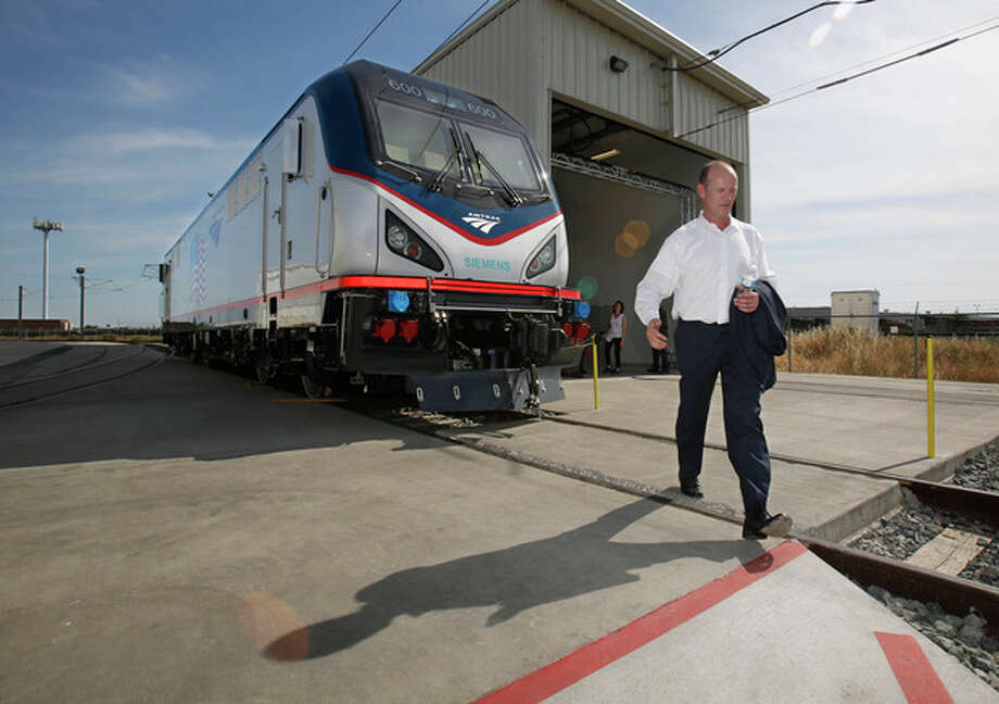 In this photo taken Saturday, May 11, 2013, Michael Cahill, president of Siemens Rail Systems, walks past one of the new Amtrak Cities Sprinter Locomotive that was built by Siemens in Sacramento, Calif. The new electric locomotive, one of three of 70 to be built, will run on the Northeast intercity rail lines and replace Amtrak locomotives that have been in service for 20 to 30 years.(AP Photo/Rich Pedroncelli) / AP