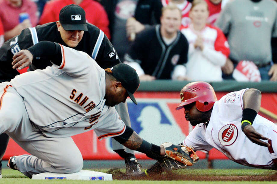 San Francisco Giants third baseman Pablo Sandoval tags out Cincinnati Reds' Brandon Phillips at third base in the first inning during Game 3 of the National League division baseball series, Tuesday, Oct. 9, 2012, in Cincinnati. (AP Photo/Michael Keating) / FR170759 AP
