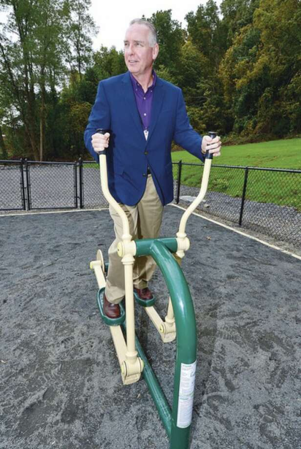 Hour photo / Erik TrautmannExecutive director of the Wilton Y, Bob McDowell, tries out one of the pieces of exercise equipment at the new Outdoor Fitness Center which officially opened Tuesday.