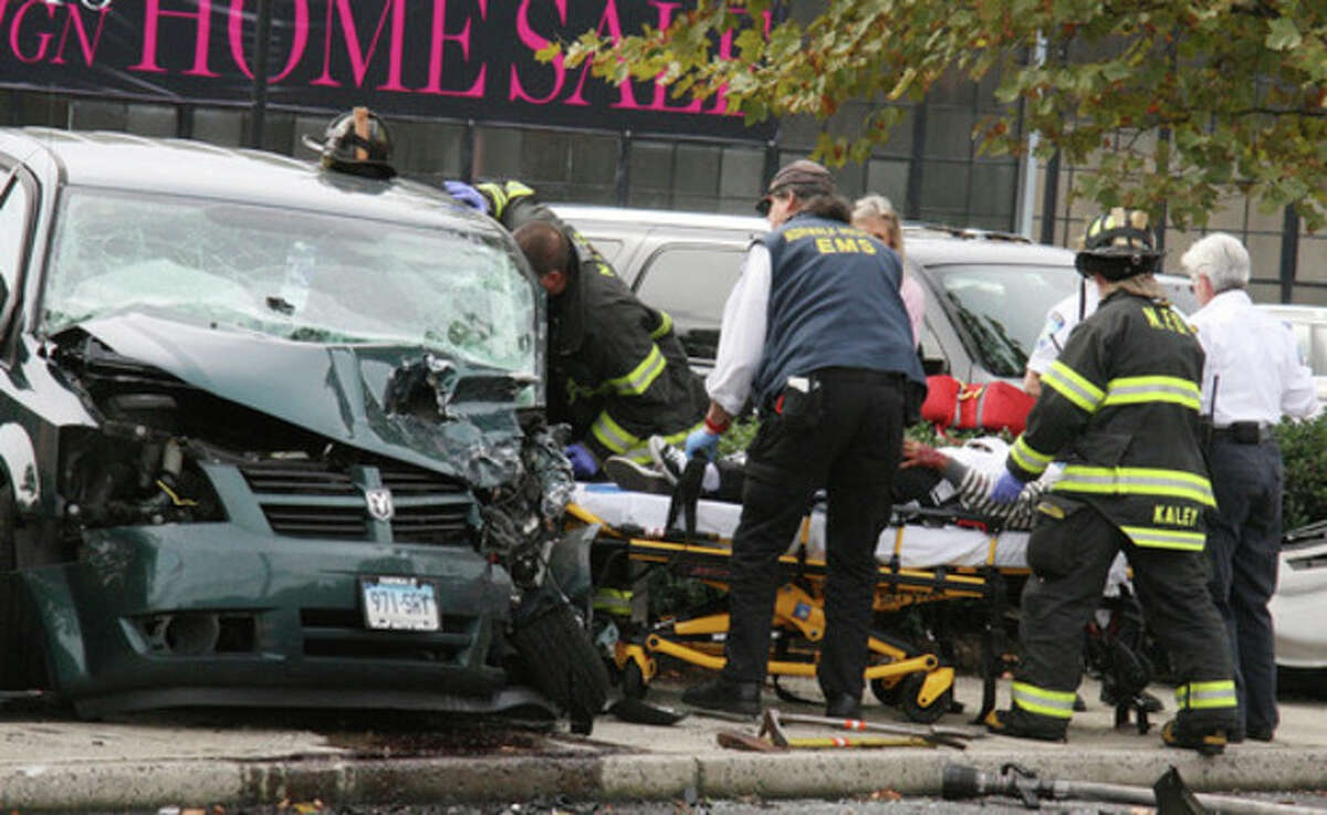 Hour Photo by Chris Bosak Norwalk firefighters and paramedics help a victim following an automobile accident on North Avenue (US Route 1) in Norwalk on Monday afternoon. Five victims were transported to Norwalk Hospital, but no serious injuries were reported.