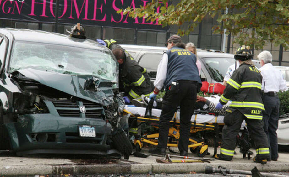 Hour Photo by Chris BosakNorwalk firefighters and paramedics help a victim following an automobile accident on North Avenue (US Route 1) in Norwalk on Monday afternoon. Five victims were transported to Norwalk Hospital, but no serious injuries were reported.