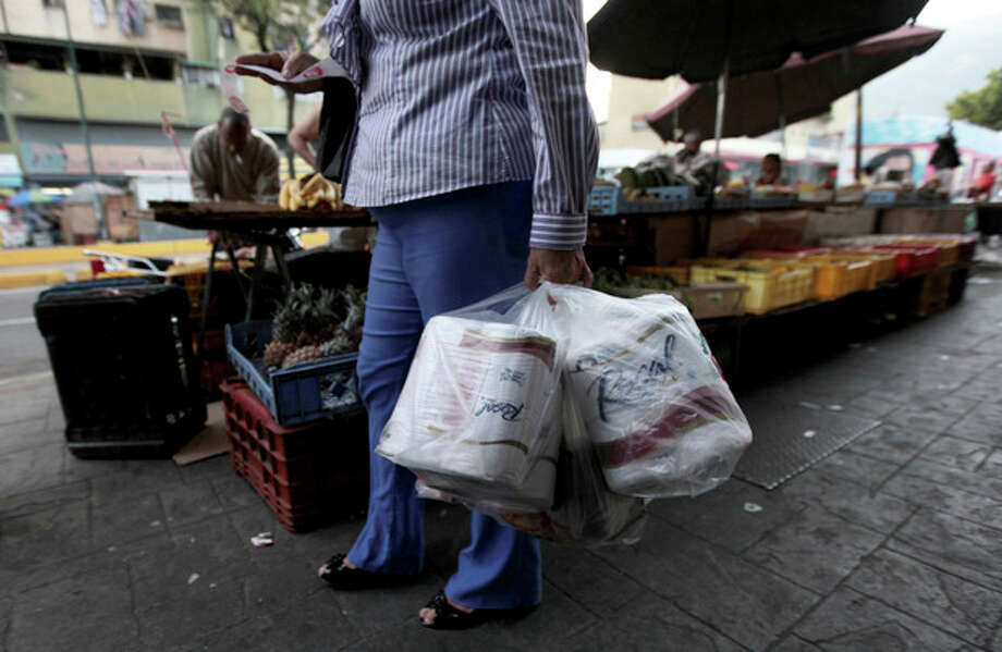 A woman who just bought toilet paper at a grocery store reads her receipt as she leaves the private store in Caracas, Venezuela, Wednesday, May 15, 2013. First milk, butter, coffee and cornmeal ran short. Now Venezuela is running out of the most basic of necessities _ toilet paper. Economists say Venezuela's shortages stem from price controls meant to make basic goods available to the poorest parts of society and the government's controls on foreign currency. (AP Photo/Fernando Llano) / AP