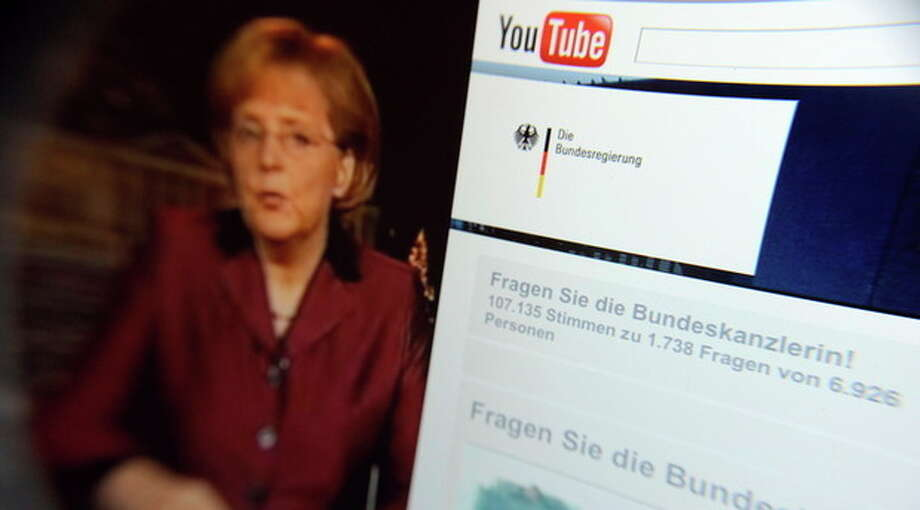 FILE- This Dec.31, 2008 file photo taken through a magnifying glass shows a video of German Chancellor Angela Merkel delivering her New Year's speech beside the Youtube channel of the German government. YouTube announced Monday, Oct. 8, 2012, that it is extending its original programming initiative into Europe, with at least 60 new video channels from media companies including Britain's BBC, London-based FreemantleMedia and the Netherlands' Endemol. The Google Inc.-owned video site said Monday it is launching more than 60 new video channels with content from Britain, Germany, France, and the United States. (AP Photo/dapd, David Hecker, File) / DAPD