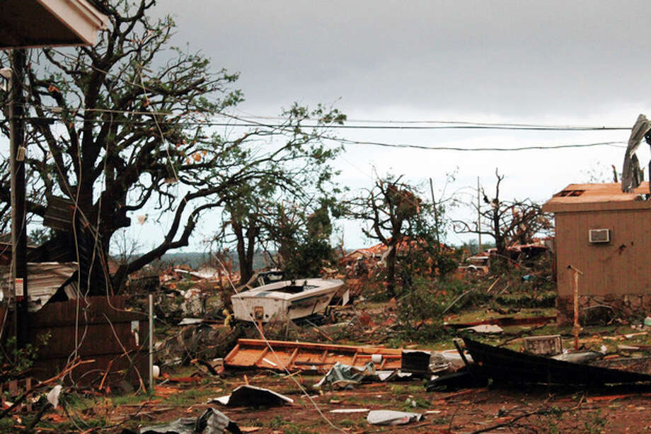 This May 16, 2013 photo provided by Nichole Tomlin shows her Granbury, Texas backyard and rubble where Tomlin says there used to be a neighborhood. A rash of tornadoes slammed into several small communities in North Texas overnight, leaving at least six people dead, dozens more injured and hundreds homeless. The violent spring storm scattered bodies, flattened homes and threw trailers onto cars. (AP Photo/Nichole Tomlin) / Nichole Tomlin