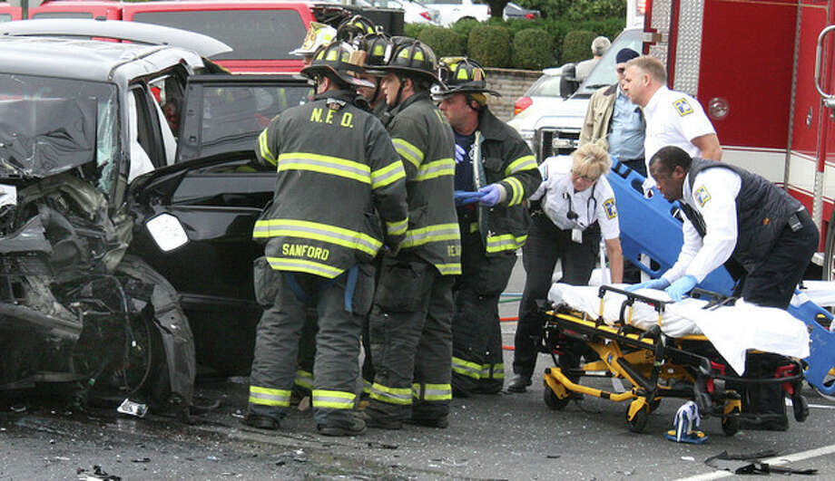 Hour Photo by Chris BosakNorwalk firefighters help an accident victim following an automobile accident on North Avenue (US Route 1) in Norwalk on Monday afternoon. Five victims were transported to Norwalk Hospital, but no serious injuries were reported.