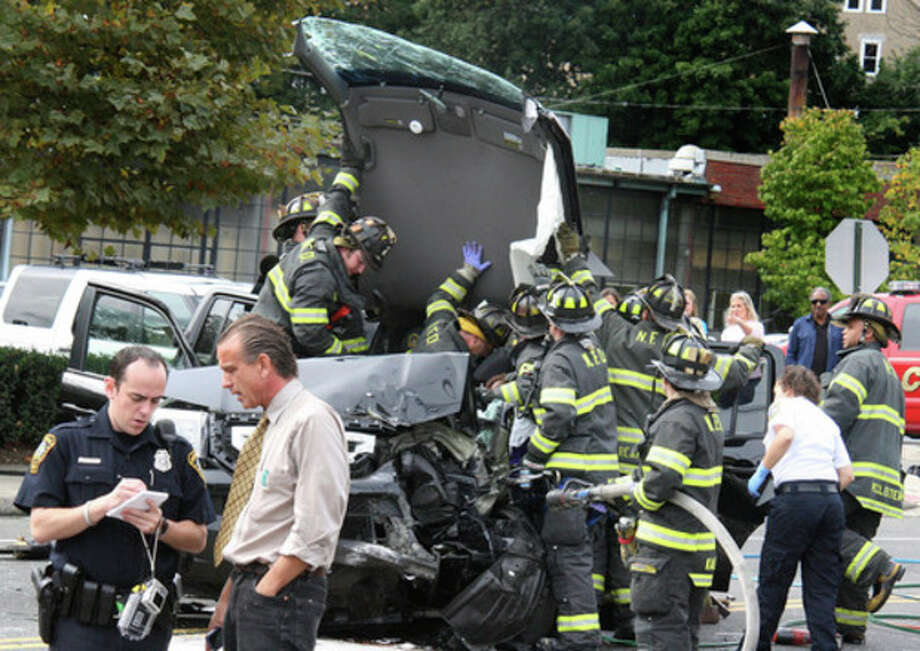 Hour Photo by Chris BosakNorwalk firefighters lift the roof off of a Honda SUV and a Norwalk Police officer takes a statement from a witness following an accident on North Avenue (US Route 1) in Norwalk on Monday afternoon. Five victims were transported to Norwalk Hospital, but no serious injuries were reported.