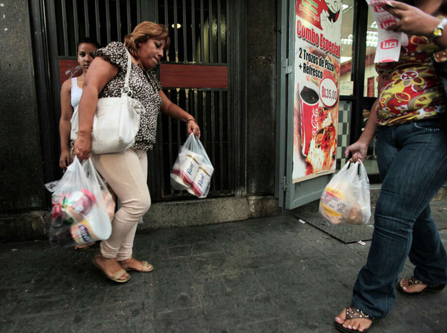 A customer leaves a private super market with her purchases, including toilet paper, in Caracas, Venezuela, Wednesday, May 15, 2013. First milk, butter, coffee and cornmeal ran short. Now Venezuela is running out of the most basic of necessities _ toilet paper. Blaming political opponents for the shortfall, as it does for other shortages, the embattled socialist government says it will import 50 million rolls to boost supplies. (AP Photo/Fernando Llano) / AP