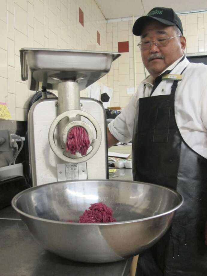 Ap photoDerek Maeda, meat manager at the Foodland Farms Aina Haina store, puts Hawaii grass-fed beef through a meat grinder in Honolulu on Sept. 28.