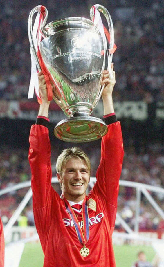 """FILE - This is a May 25, 1999 file photo of Manchester United's midfielder David Beckham holding the winner's cup, after his side defeated Bayern Munich in their Champions League final football match, at the Nou Camp stadium. David Beckham is retiring from soccer after the season, ending a career in which he become a global superstar since starting his career at Manchester United. The 38-year-old Englishman recently won a league title in a fourth country with Paris Saint-Germain. He said in a statement Thursday May 16, 2013 he is """"thankful to PSG for giving me the opportunity to continue but I feel now is the right time to finish my career, playing at the highest level."""" (AP Photo/Phil Noble/PA, File) UNITED KINGDOM OUT NO SALES NO ARCHIVE"""