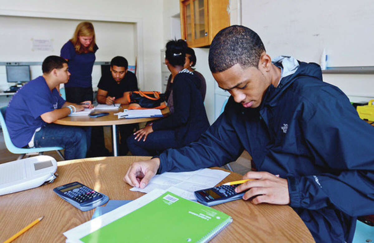 Omar Reid works on his math problem during Ms. Lay-Alaimo's math class at Briggs High School Friday. With Briggs moving toward a career academy, more students are choosing to go to the alternative high school. Hour photo / Erik Trautmann