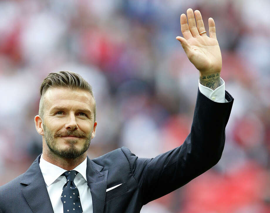FILE - In this June 2, 2012 file photo, England's David Beckham gestures during a ceremony to honor the five players that have played for England over 100 times each during the international friendly soccer match between England and Belgium at Wembley Stadium in London. Beckham says he is retiring from soccer at the end of the season. The 38-year-old Beckham recently won a league title in a fourth country with Paris Saint-Germain. He has become a global superstar since starting his career at Manchester United.(AP Photo/Kirsty Wigglesworth, File) / AP