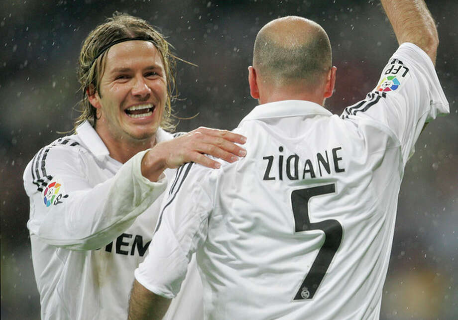 """FILE - This is a Sunday, Jan. 15, 2006 file photo of Real Madrid's David Beckham, left, as he congratulates goalscorer Zinedine Zidane during their Spanish league soccer match against Sevilla at the Santiago Bernabeu Stadium in Madrid, Spain. David Beckham is retiring from soccer after the season, ending a career in which he become a global superstar since starting his career at Manchester United. The 38-year-old Englishman recently won a league title in a fourth country with Paris Saint-Germain. He said in a statement Thursday May 16, 2013 he is """"thankful to PSG for giving me the opportunity to continue but I feel now is the right time to finish my career, playing at the highest level."""" (AP Photo/Bernat Armangue, File) / AP"""