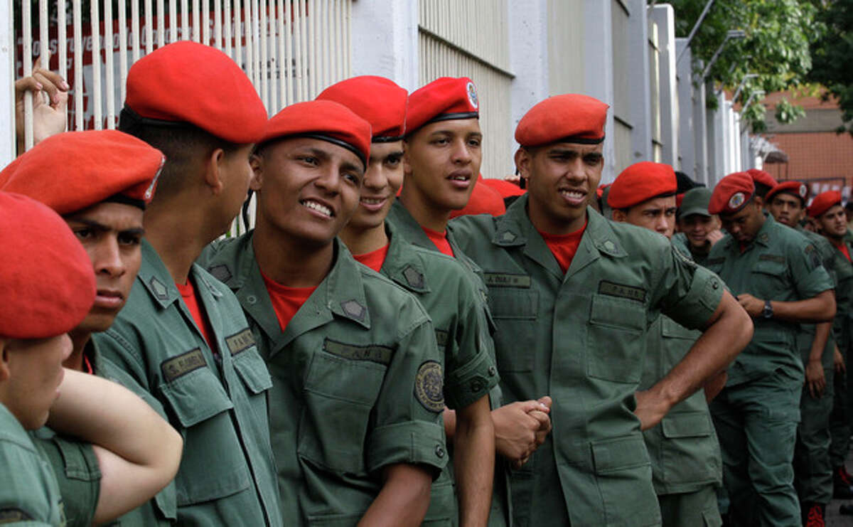 Presidential guards wait in line to vote in the presidential election at a polling station in Caracas, Venezuela, Sunday, Oct. 7, 2012. President Hugo Chavez is running against opposition candidate Henrique Capriles. (AP Photo/Fernando Llano)