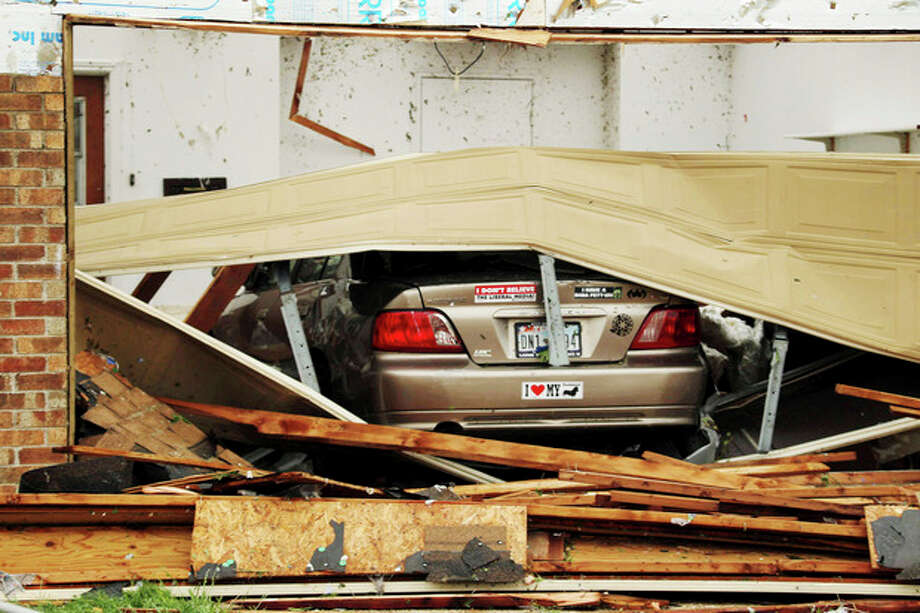 A car is seen in a damaged home after Wednesday's tornado in Cleburne, Texas on Thursday, May 16, 2013. Ten tornadoes touched down in several small communities in Texas overnight, leaving at least six people dead, dozens injured and hundreds homeless. Emergency responders were still searching for missing people Thursday afternoon. (AP Photo/Ron Russek II) / AP