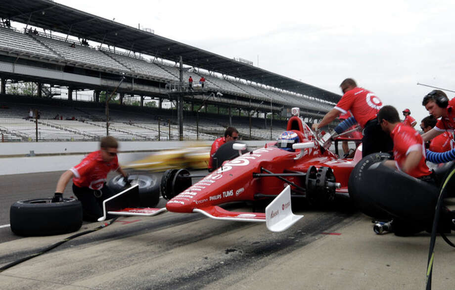 A car drives by as the crew of Scott Dixon, of New Zealand, practices a pit stop during practice for the Indianapolis 500 auto race at the Indianapolis Motor Speedway in Indianapolis, Thursday, May 16, 2013. (AP Photo/Darron Cummings) / AP