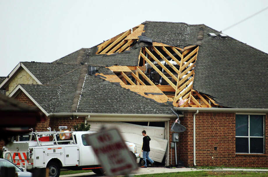 A man walks in front of a home damaged by Wednesday's tornado in Cleburne, Texas on Thursday, May 16, 2013. Ten tornadoes touched down in several small communities in Texas overnight, leaving at least six people dead, dozens injured and hundreds homeless. Emergency responders were still searching for missing people Thursday afternoon. (AP Photo/Ron Russek II) / AP