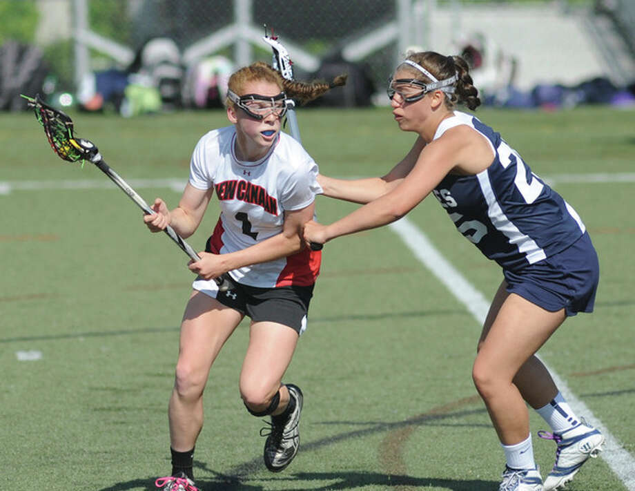 Hour photo/John NashNew Canaan's Liz Miller, left, protects the ball from Staples defender Ali Aprile during Thursday's FCIAC girls lacrosse quarterfinal at Dunning Field in New Canaan. The host Rams won, 12-5.
